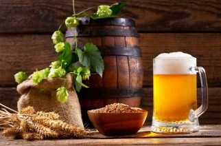 Mug of beer with green hops, wheat ears and wooden barrel on wooden background